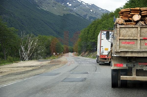 Un camión traslada madera sin red de contención. Delante suyo, otro camión de gran porte.