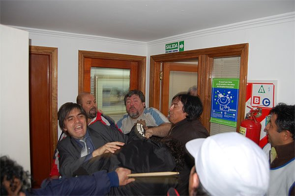 Paulino Rossi intenta frenar a uno de los enardecidos manifestantes.